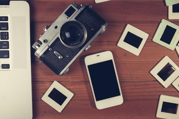 Retro camera en enkele oude foto's op houten tafel