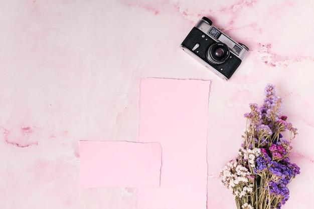 Retro camera in de buurt van papieren en bos bloemen