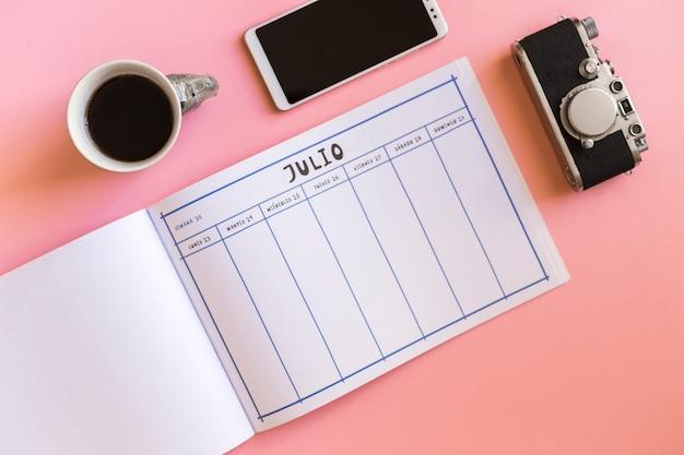 Retro camera in de buurt van smartphone, cup en kalender