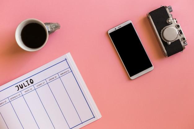 Retro camera in de buurt van smartphone, kopje drank en kalender