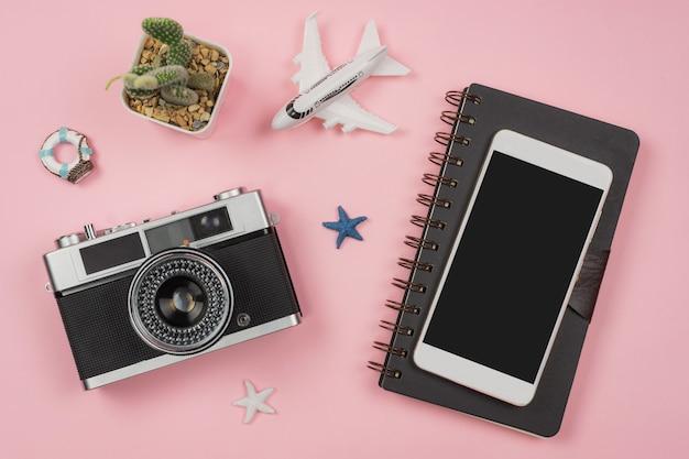 Retro camera met speelgoedvliegtuig op pastel roze achtergrond met reisdagboek