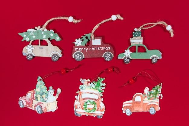 Retro collectie van speelgoedauto's kerstspeelgoed op kerstboom op rode achtergrond