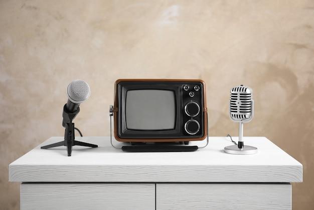 Retro draagbare tv en microfoons op tafel tegen lichte muur