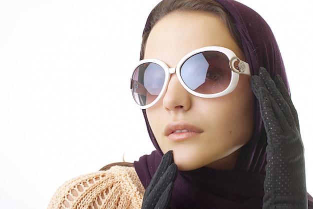 Retro elegante modieuze vrouw met glazen in studio