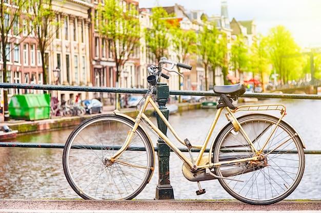 Retro fiets op de brug in amsterdam, nederland tegen een kanaal