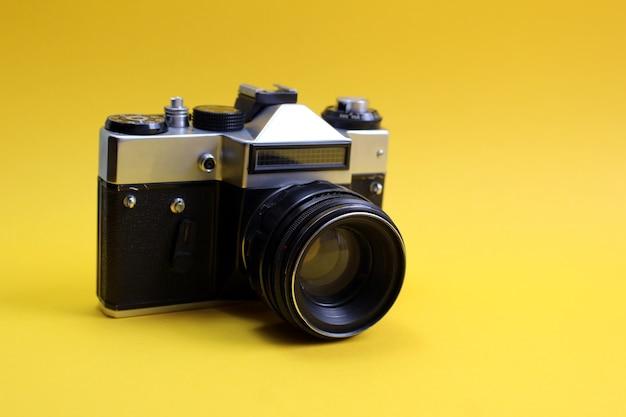 Retro fotocamera op een gele achtergrond.