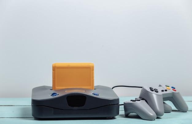 Retro gameconsole en gamepads op een witte muur. retro gamen