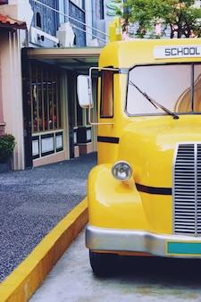 Retro gele oude glanzende glimmende dichte omhooggaand van de schoolbus