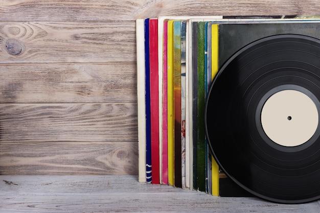 Retro gestileerd beeld van een inzameling van oude vinylverslaglp's met kokers op een houten achtergrond.