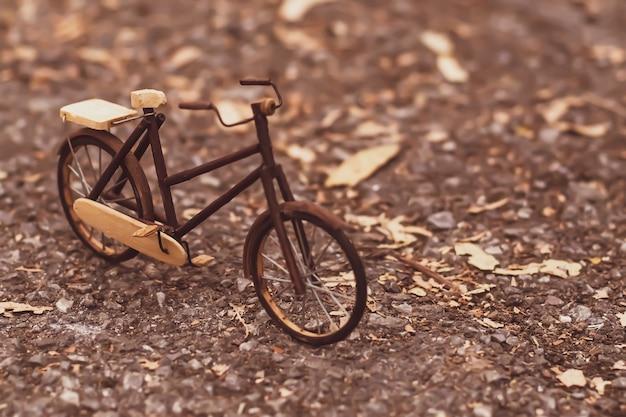 Retro gestileerd beeld van een met de negentiende eeuw met de hand gemaakte die fiets op aardachtergrond wordt geïsoleerd