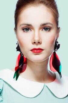 Retro gestileerd portret van een jonge vrouw die mooie plastic oorbellen draagt