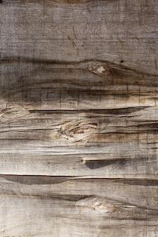 Retro houten achtergrond, gebarsten multiplex muur onder de zon
