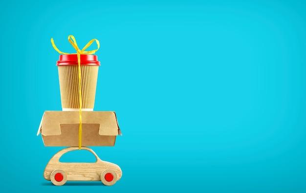 Retro houten speelgoedauto die bestelling levert papieren koffiekopje en voedseldoos op blauwe achtergrond. ruimte kopiëren
