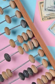 Retro houten telraam, dollarbiljetten op een gekleurd papier