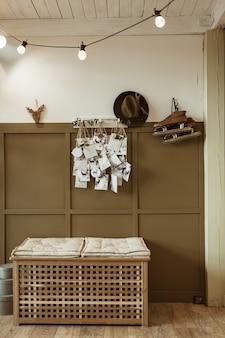 Retro interieurconcept met witte en bruine muur, schaatsen, hoed, ansichtkaarten, lichten, rotan ligstoel