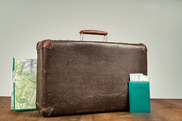 Retro koffer met kaart en paspoort met geld