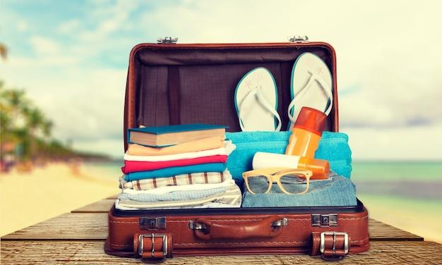 Retro koffer met reisvoorwerpen op zee achtergrond