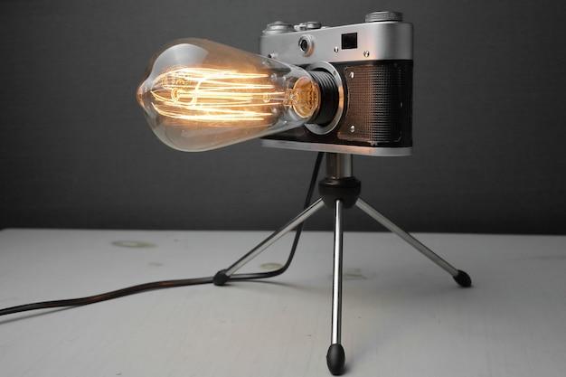 Retro lamp van een oude camera met een edison lamp op een grijze achtergrond.