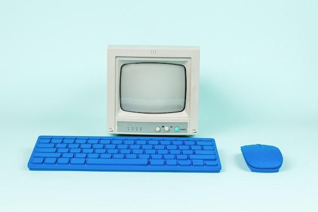 Retro monitor en blauw toetsenbord met muis op een lichte achtergrond.