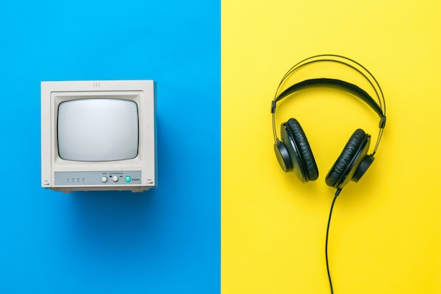 Retro monitor en zwarte koptelefoon op gele en blauwe achtergrond. set van oude radioapparatuur.