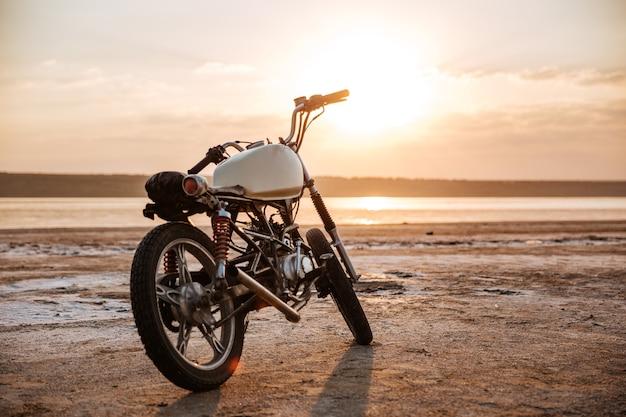 Retro motorfiets die zich in de woestijn bij zonsondergang bevindt