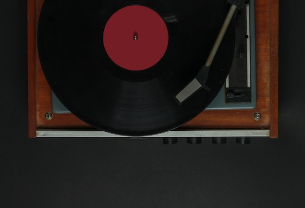 Retro muziekspeler. vinyl platenspeler met een vinyl record op een zwarte achtergrond. jaren 70. bovenaanzicht