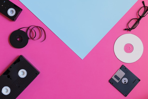 Retro opslagapparaten: twee videocassettes, diskettes, cd's en brillen. verouderd technologieconcept op roze blauwe gekleurde document achtergrond