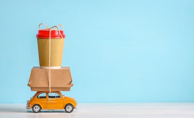 Retro oranje speelgoedauto die fastfood-papieren koffiekopje en voedseldoos op blauwe achtergrond levert. ruimte kopiëren