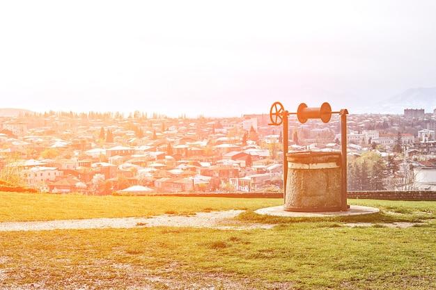 Retro oude put op de achtergrond van het stadspanorama kutaisi georgië zon flare