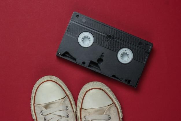 Retro oude sneakers en vhs op rode achtergrond. jaren 80. bovenaanzicht