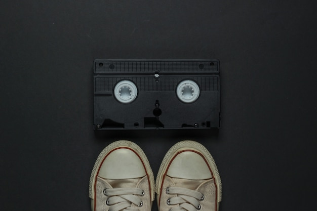 Retro oude sneakers en videocassette op zwarte achtergrond. jaren 80. bovenaanzicht