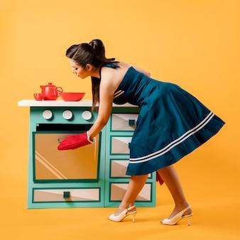 Retro pinupmeisje in de keuken