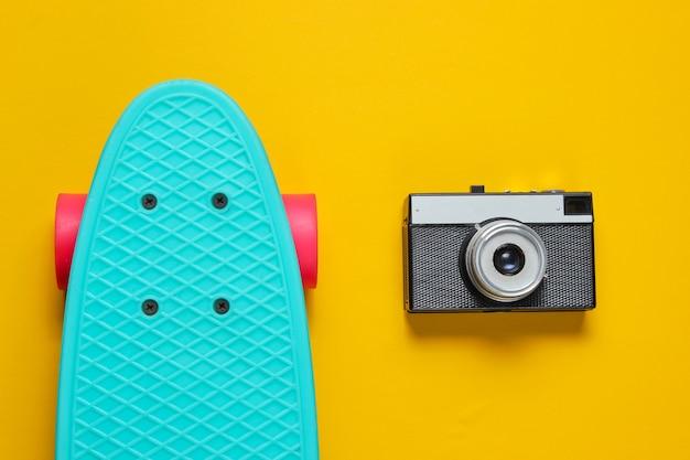 Retro reeks met blauw skateboard en retro camera op gele achtergrond. studio opname. jeugd levensstijl. bovenaanzicht