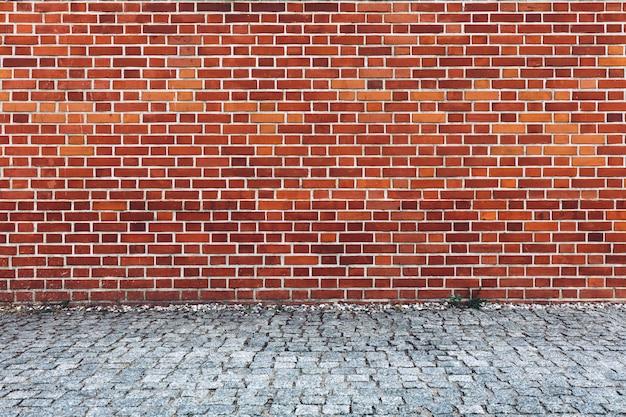 Retro rode bakstenen muur en keibestrating.