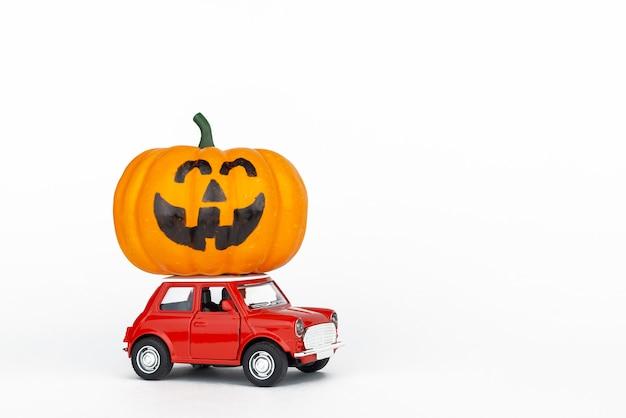 Retro rode speelgoedauto met een pompoen
