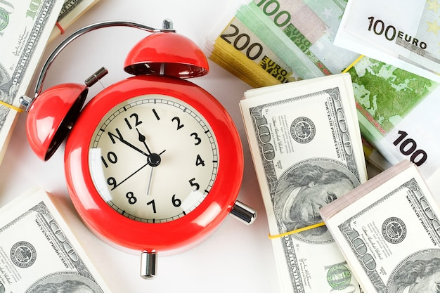 Retro rode wekker en stapels dollar en eurobankbiljetten