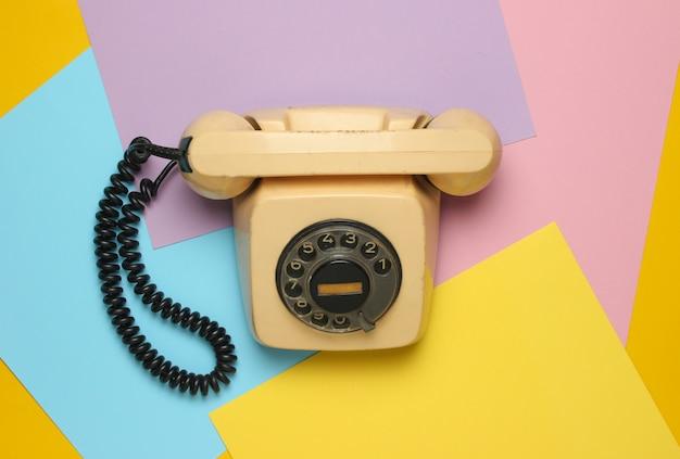 Retro roterende telefoon uit de jaren 80 op een gekleurd pastel oppervlak. bovenaanzicht, minimalisme