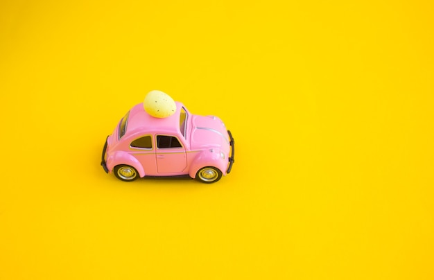 Retro roze speelgoedauto met paasei op het dak. paaskaart met ruimte voor tekst op een gele achtergrond.