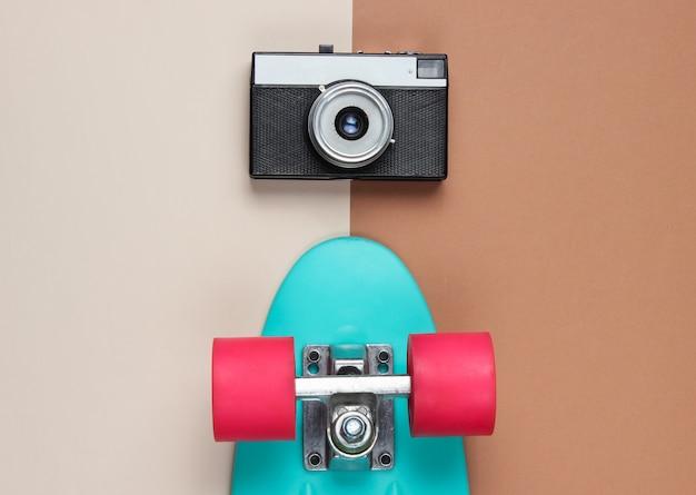Retro set met blauw skateboard en retro camera op gekleurde achtergrond. studio opname. jeugd levensstijl. bovenaanzicht