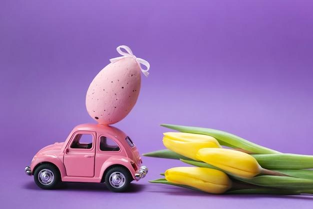 Retro speelgoedauto op een paarse ondergrond