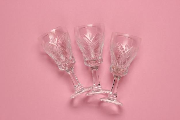 Retro stijl facetgeslepen kristallen wijnglazen op roze pastel achtergrond.