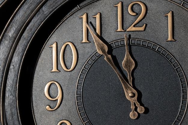 Retro-stijl klok met goudachtige cijfers die vijf minuten voor middernacht aangeven