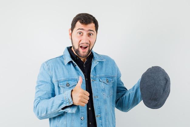 Retro-stijl man die zijn pet vasthoudt terwijl hij zijn duim in jas, pet laat zien en er respectvol uitziet. vooraanzicht.