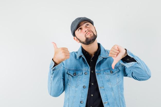 Retro-stijl man in jas, pet, shirt met duim op en neer en kijkt verward, vooraanzicht.