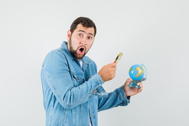 Retro-stijl man in jas, t-shirt kijken naar mini wereldbol met vergrootglas en verbaasd kijken.