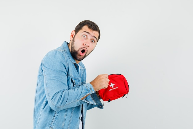 Retro-stijl man op zoek naar ehbo-kit in jasje, t-shirt en verrast op zoek.