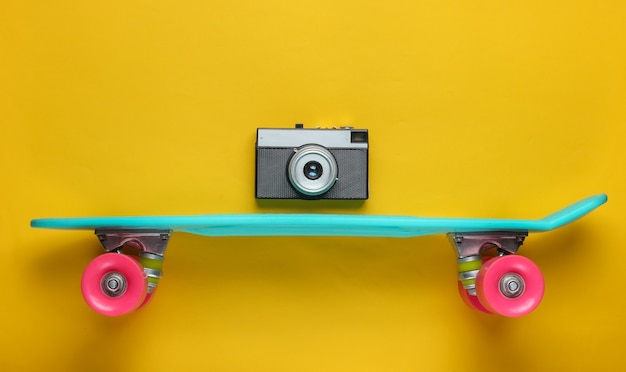 Retro stijl. plastic minikruiserraad en retro camera op gele achtergrond. pastelkleurige trend. zomerplezier. minimalistisch jeugdconcept.