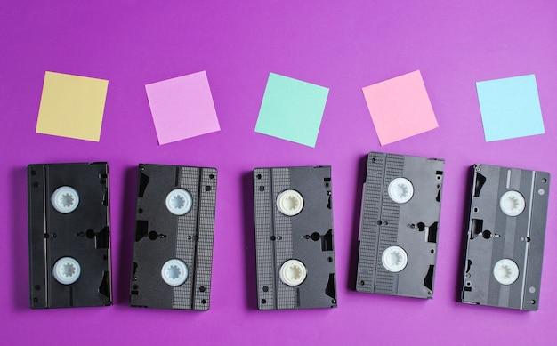 Retro stijl, pop-art concept. audiocassettes en memopapier op paars. bovenaanzicht.