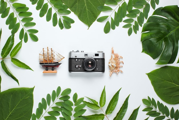 Retro-stijl reisstilleven. filmcamera, schelpen, groene tropische bladeren. reizigerstoebehoren op een witte achtergrond.