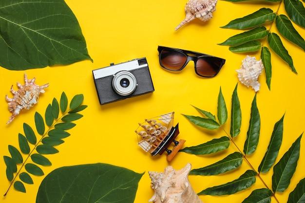 Retro-stijl reisstilleven. filmcamera, zonnebril, schelpen, groene tropische bladeren. reizigerstoebehoren op gele achtergrond.
